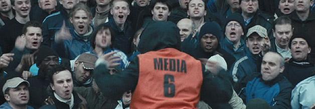 Hooligans beschäftigt sich nicht primär, aber auch mit der Rolle der Medien. Hier nutzt ein Hooligan eine Presse-West, um sich an den gegnerischen Fanblock herunzumachen.