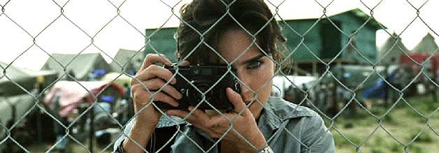 Das Bild zeigt die Journalistin Maddy Bowen aus dem Film Blood Diamond. Hier steht sich hinter dem Maschendrahtzaun eines Flüchtlingslagers. Die Kamera ist gezückt.
