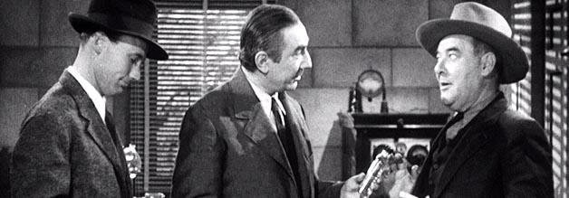 Bela Lugosi im Kreuzverhör: Reporter Layton (links) und Fotograf McGuire (rechts) ermitteln im Fall einer Monsterfledermaus. Die Spur führt zum dubiosen Duftwasserkomponisten Carruthers.